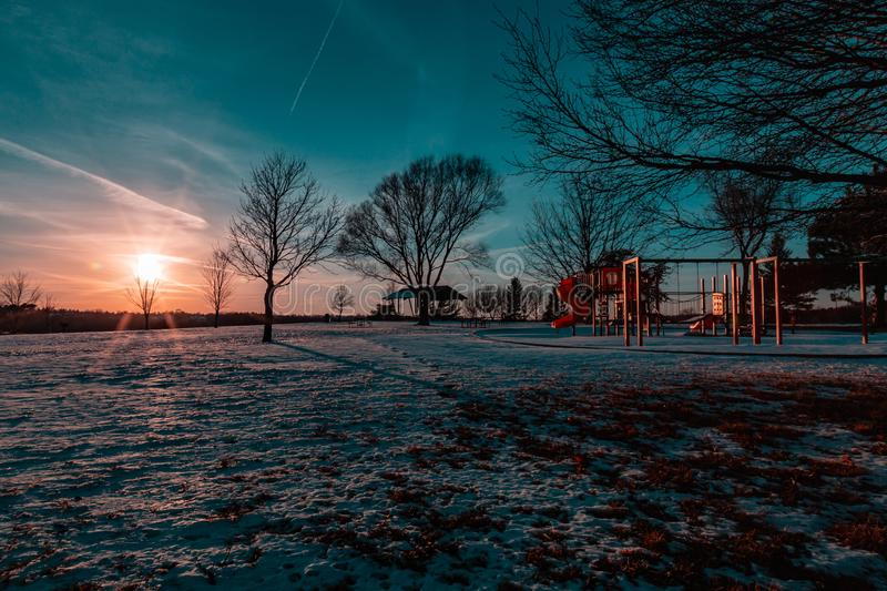 Sunset in winter with beautiful skyline over lake Zorinsky Omaha Nebraska. Sunset in winter with beautiful clouds in the sky and snow on ground. Children stock photography