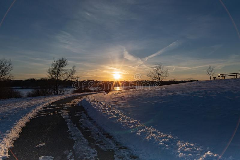 Sunset in winter with beautiful skyline over lake Zorinsky Omaha Nebraska. Sunset in winter with beautiful clouds in the sky and snow on ground. Cleared path royalty free stock photography