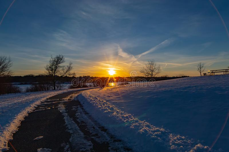 Sunset in winter with beautiful skyline over lake Zorinsky Omaha Nebraska. Sunset in winter with beautiful clouds in the sky and snow on ground. Cleared path royalty free stock images