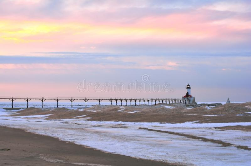 Sunset at Winter Lighthouse. A far-off lighthouse is pictured in winter under a colorful sky as its light begins to come on at sunset. There is a snowy beach in royalty free stock photos