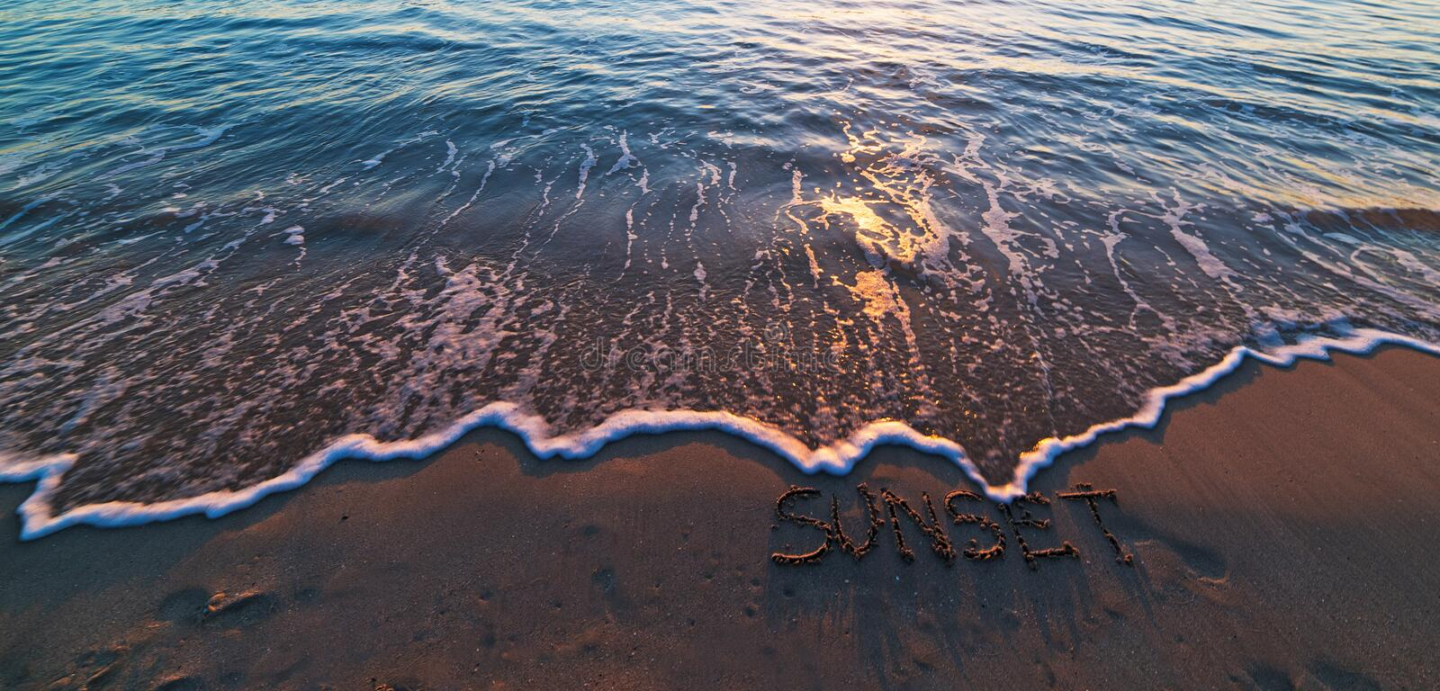 Sunset written in the sand. Sunset with small waves at the beach royalty free stock photos