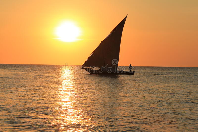 Sunset on a Zanzibar beach. A dhow sails through the sunset at Stone town Zanzibar stock photos