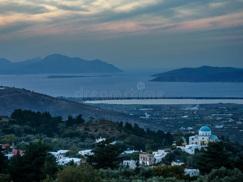 Sunset from Zia Kos to the Aegean Sea. Image of a soft pink blue sunset. Taken from the Town of Zia with silhouette of the Turkish mainland. There is a village stock images