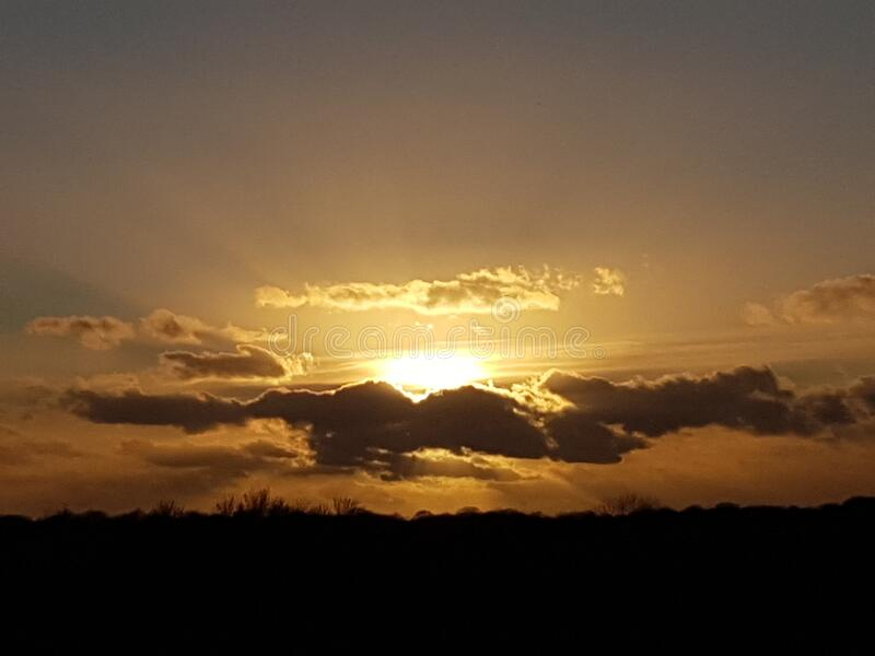 The sunsets over Hatfield forest on this winters evening golden clouds and sun beams stock photos