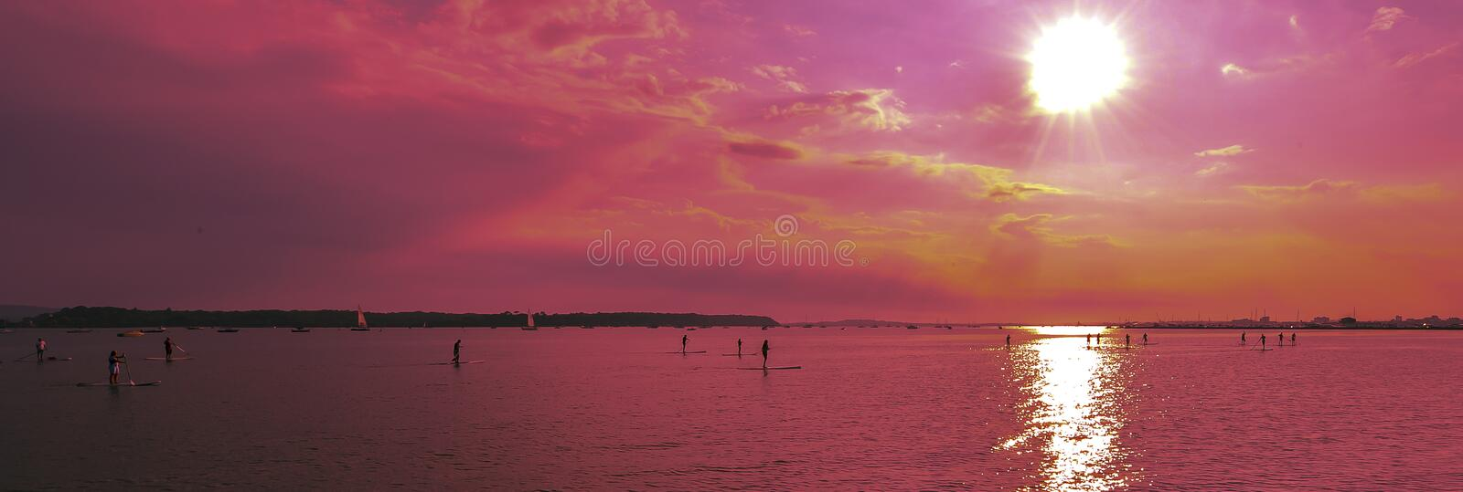 Sunsets over paddlebroaders stock photography