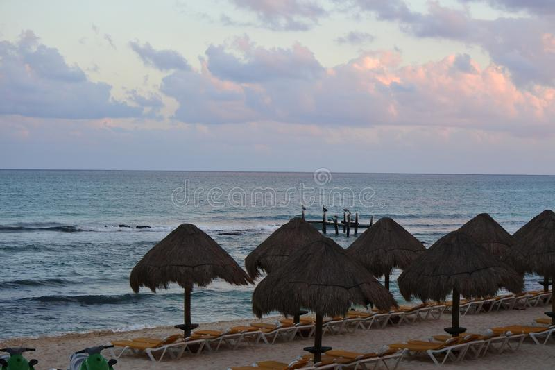 Sunsetting over blue ocean water on the beach. With yellow lawn chairs and huts stock images
