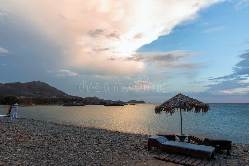 Sunshade on empty beach in the evening. stock photos