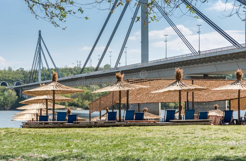 Sunshades or parasols on the Strand city beach in Novi Sad, Serbia with bridge and blue sky above ready for swimming summer season royalty free stock image