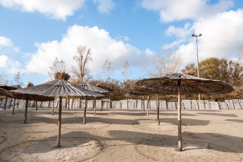 Sunshades of parasols van riet op het lege zandige strand dichtbij water met zonnige blauwe hemel met wolken voor recreatieve vri stock fotografie