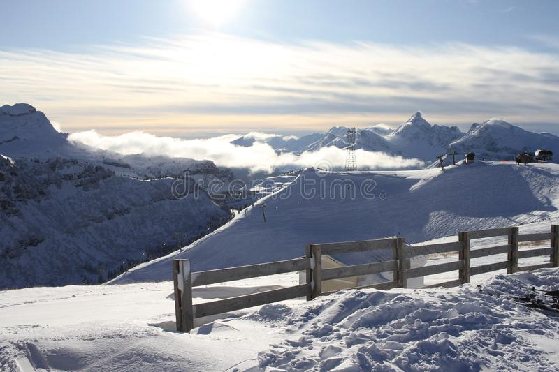 Sunshine and clouds on the Tetes Des Saix 2118m ski run above Samoens in the French Alps. View to Grandes Jorasses Mountain Range with a fence in the stock images