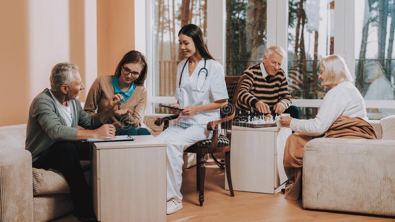 Sunshine Day Nursing Home. Old People Play Chess. Sunshine Day in Nursing Home. Old People Play Chess. Elderly Man Bequeaths House Keys. Black-Haired Doctor royalty free stock photos