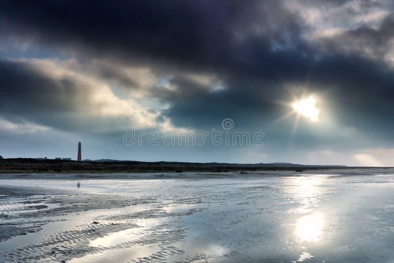 Sunshine door donkere stormwolken boven vuurtoren royalty-vrije stock fotografie