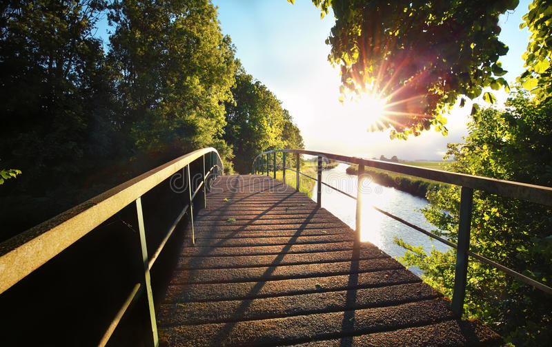 Sunshine over bridge and river royalty free stock photos