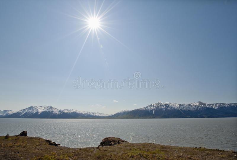 Sunshine over Cook Inlet. Scenic view of sun shining over Cook ocean inlet with snow capped Turnagain Arm mountain range in background, Alaska, U.S.A stock photography