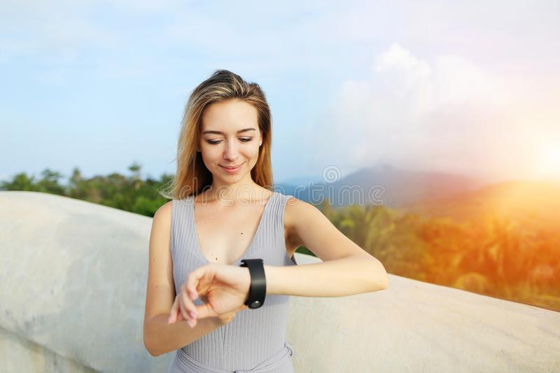 Sunshine portrait of young blonde woman using smartwatch, mountains in background, Thailand. royalty free stock photography
