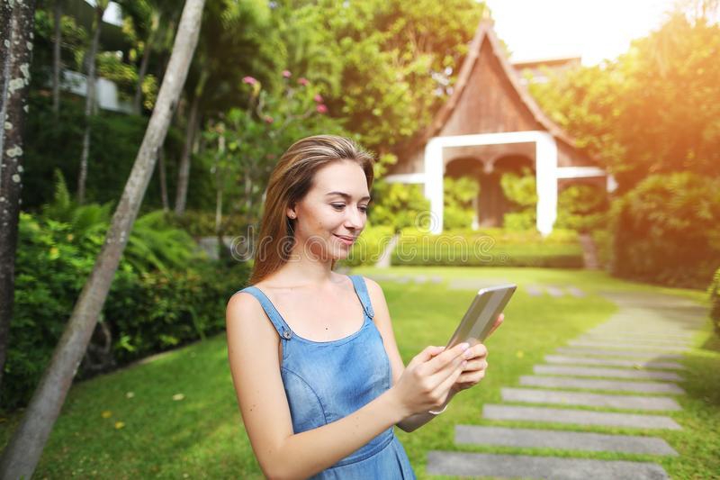Sunshine portrait of young woman using tablet and smiling on green palms and house background in Thailand stock photography