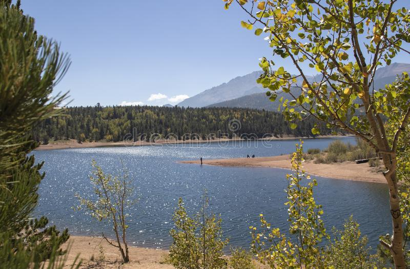 Sunshine sparkles on the water a fisheman stands on a point and aspen leaves turning yellow shimmer at Chrystal Reservoir half way. Up Pikes Peak mountain near stock images