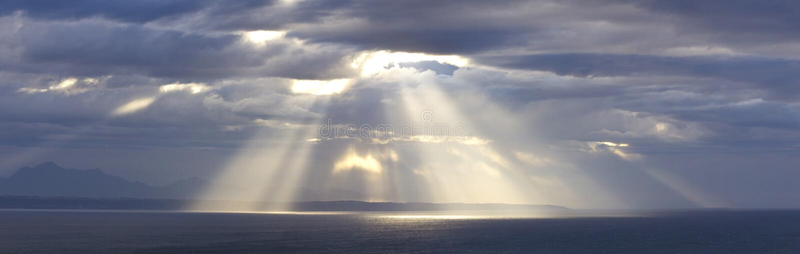 Sunshine through storm clouds stock photo