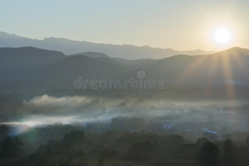 Sunshine to the foggy hill stock photo