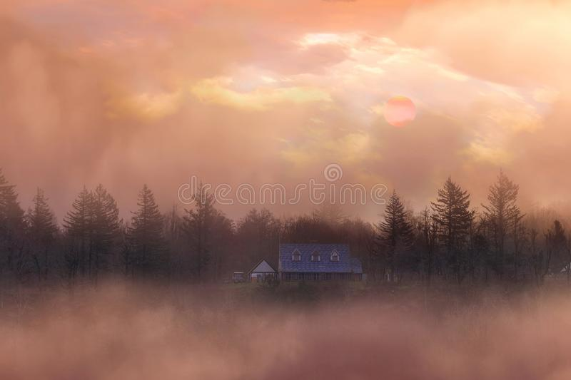 Sunsrise over Homestead in Columbia River Gorge in Oregon. Foggy sunrise over homestead on a hill in Columbia River Gorge Oregon royalty free stock image
