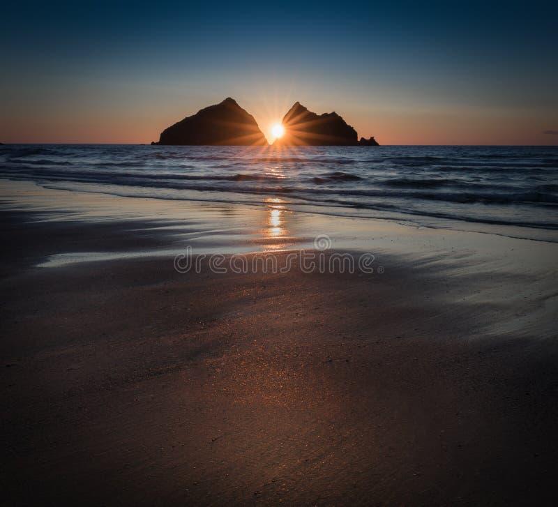 Sunstar zmierzch odbija nad opustoszałą plażą, Holywell zatoka, Cor fotografia stock