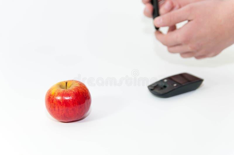 Sunt äpple i fokusen, caucasianhänder i bakgrunden med glucometer arkivbild