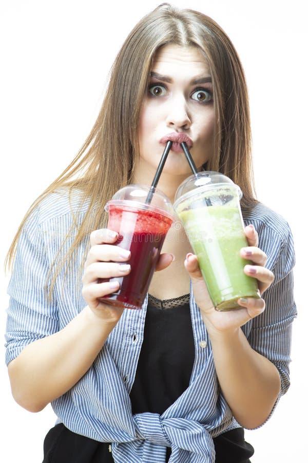 Sunt äta för mat Gullig och rolig Caucasian kvinna som dricker med både den gröna och röda Detoxgrönsaksmoothien royaltyfria bilder