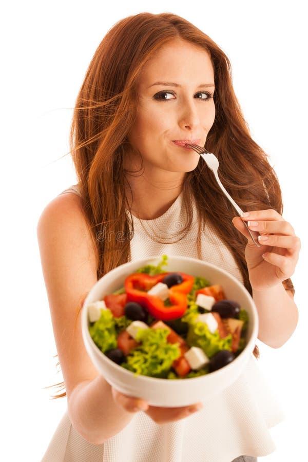 Sunt äta - kvinnan äter en bunke av grekisk sallad som över isoleras arkivfoton