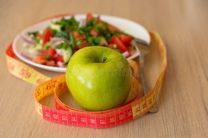 Sunt äta och att banta och att banta och väger upp förlustbegreppet - som är nära av det gröna äpplet och att mäta bandet och sal arkivfoton