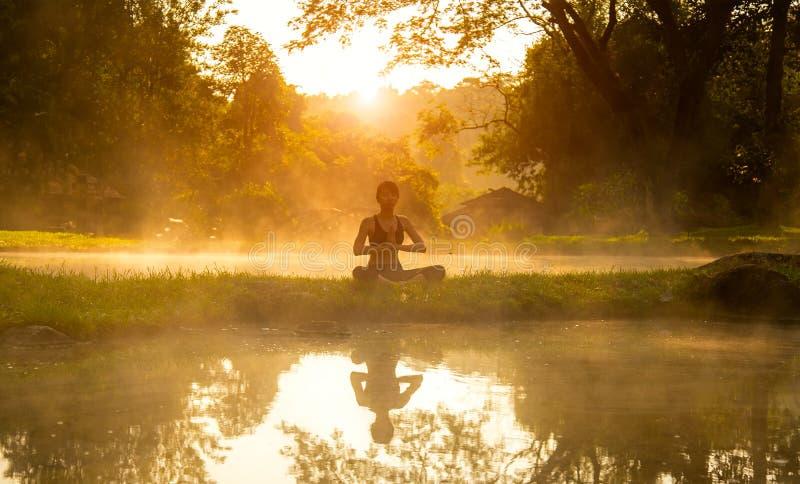 Sunt öva för kvinnalivsstil som är livsviktigt mediterar, och energiyoga i morgon vårnaturbakgrunden royaltyfri fotografi