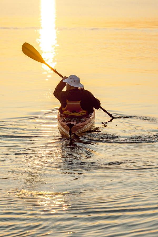 Sunt aktivt hav för hög man som kayaking på soluppgång, eller solnedgång Utomhus- tycka om för affärsföretagvattensportar som är  royaltyfri bild