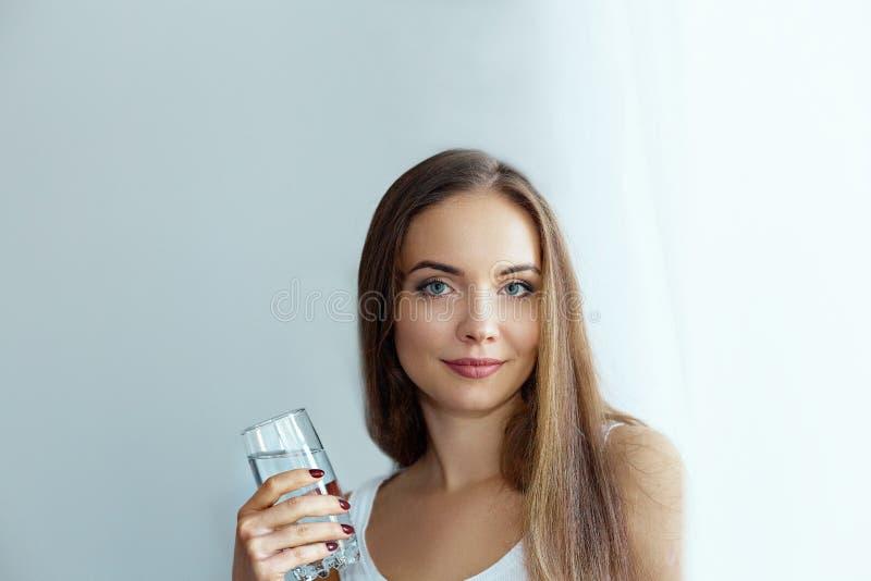 Sunt banta n?ring Stående av den härliga unga kvinnan som tar vitaminpillret som ser i fönster royaltyfria foton