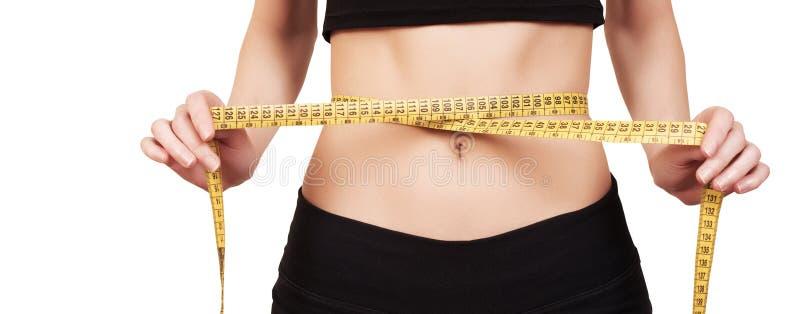 sunt begrepp hur livsstilar förlorade mycket visande viktkvinna Konditionflicka som mäter hennes midja med måttbandet, isolat fotografering för bildbyråer