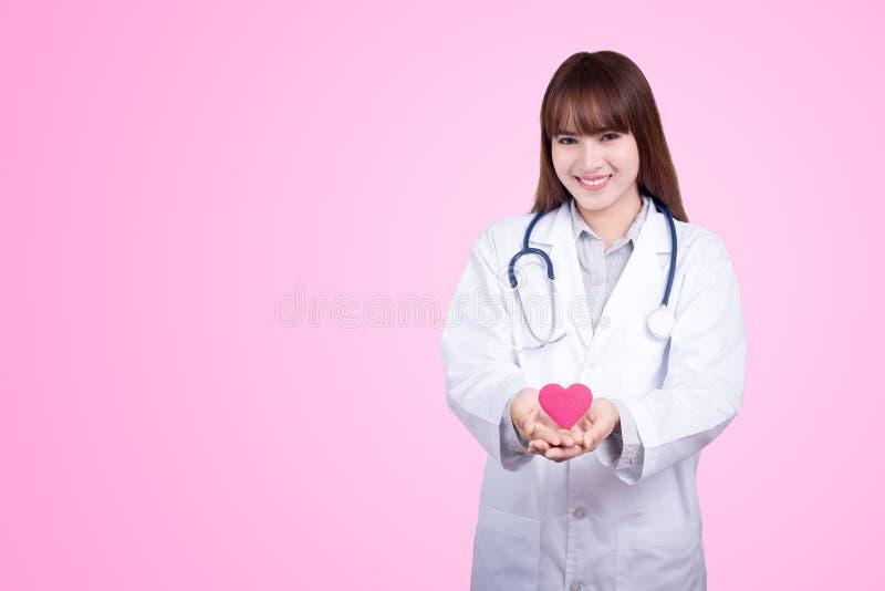 Sunt begrepp: Ung asiatisk doktor med röd hjärta i hand royaltyfria foton