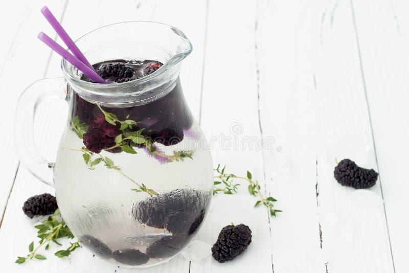 Sunt detoxvatten med mullbärsträdet Kall uppfriskande bärdrink med is och timjan på den vita trätabellen Rent äta arkivbild