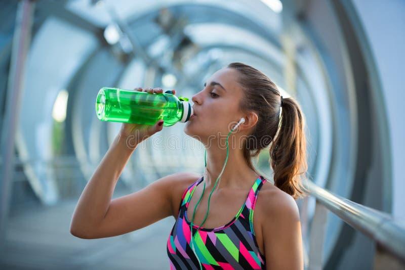 Sunt dricksvatten för ung kvinna och lyssna till musik, når att ha övat royaltyfria bilder