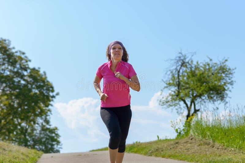 Sunt färdigt tycka om för kvinna joggar i solsken royaltyfri bild