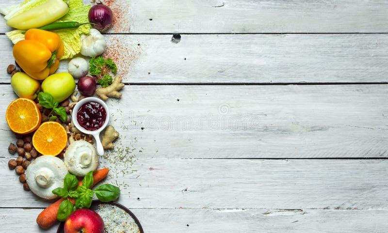Sunt färgrika sunda örter för äta -, kryddor, frukter och grönsaker på den vita trätabellen royaltyfria bilder