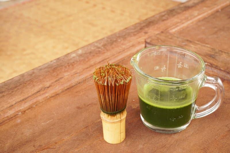 Sunt grönt te i kopp och bambu viftar arkivbild