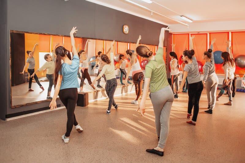 Sunt livsstilbegrepp för barn - grupp av sportive av tonårs- flickor som övar i idrottshallen royaltyfria foton