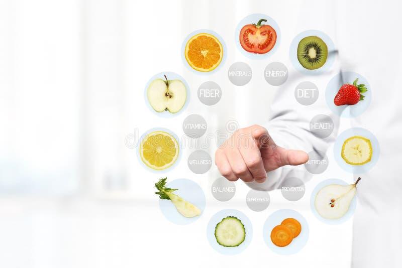 Sunt matbegrepp, hand av näringsfysiologdoktorn som pekar frukt fotografering för bildbyråer