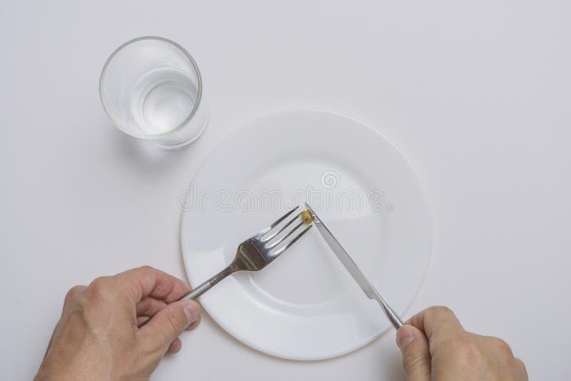 Sunt mattema: h?nder som rymmer kniven och gaffeln p? en platta med gr?na ?rtor p? en vit b?sta sikt f?r tabell royaltyfri foto