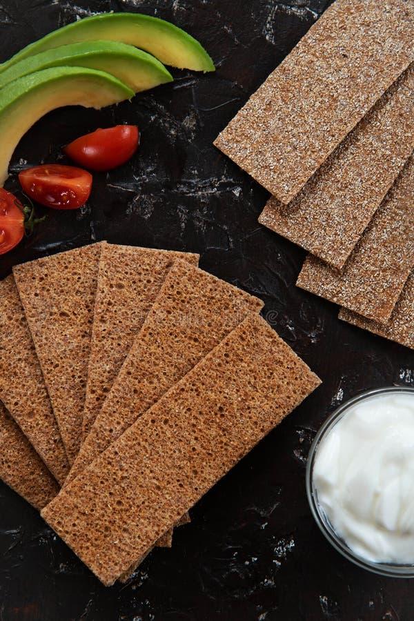 Sunt mellanmål från den wholegrain rågknäckebrödsmällaren med med ingredienser för sandwicht på svart bakgrund arkivbilder
