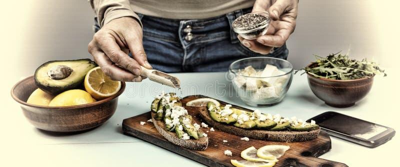 sunt mellanmål Kvinnan förbereder smörgåsar med avokadot och arugula hemma arkivfoto