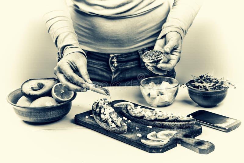 sunt mellanmål Kvinnan förbereder smörgåsar med avokadot och arugula hemma royaltyfri foto