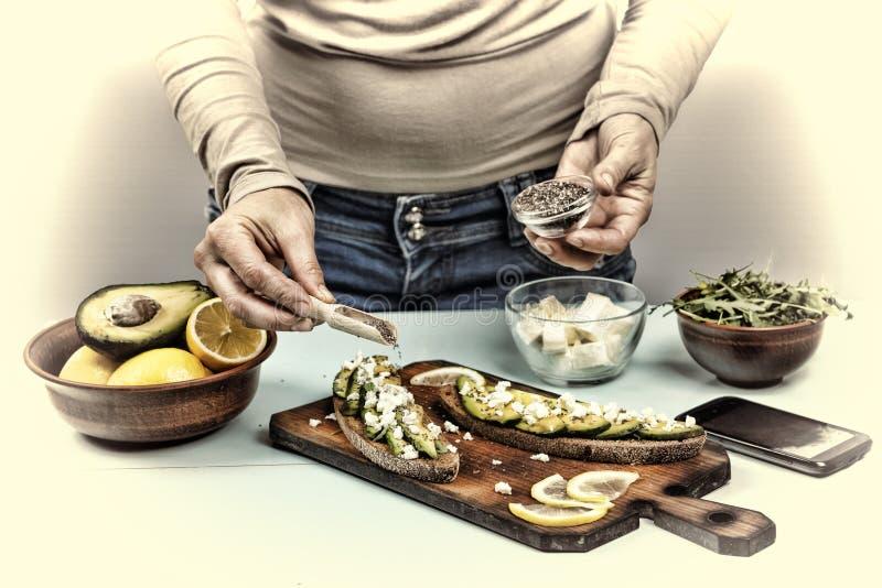 sunt mellanmål Kvinnan förbereder smörgåsar med avokadot och arugula hemma royaltyfri fotografi