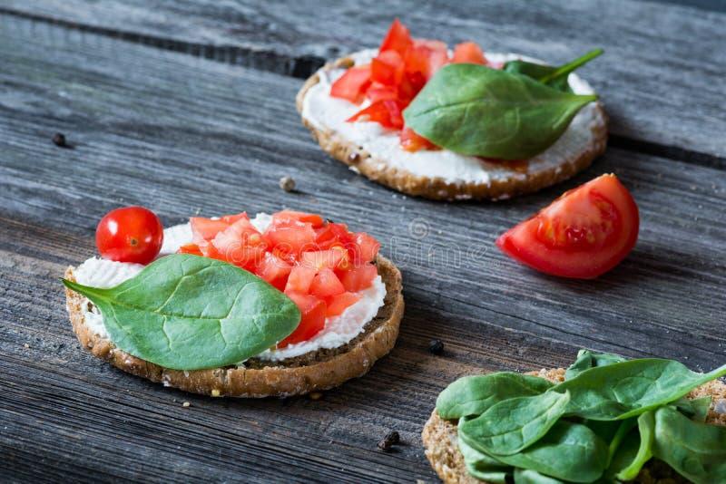 Sunt mellanmål med spenat, tomaten, ricotta och helt kornbröd royaltyfri fotografi