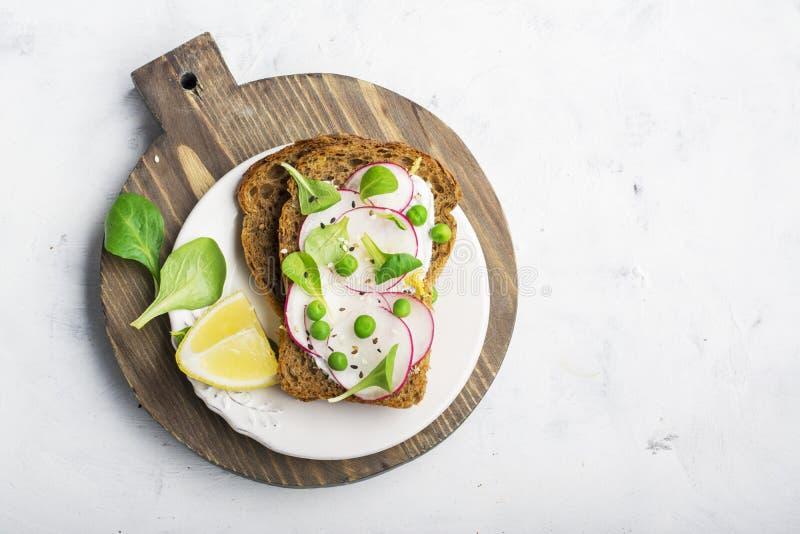 Sunt mellanmål: skivakornbröd med ricotta, gröna ärtor, rädisor, citronpiff och fruktsaft Top beskådar royaltyfri bild