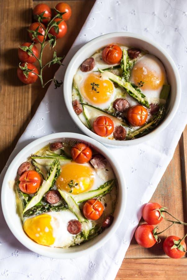 Sunt och rich frukostera med bakade ägg och grönsaker arkivfoto