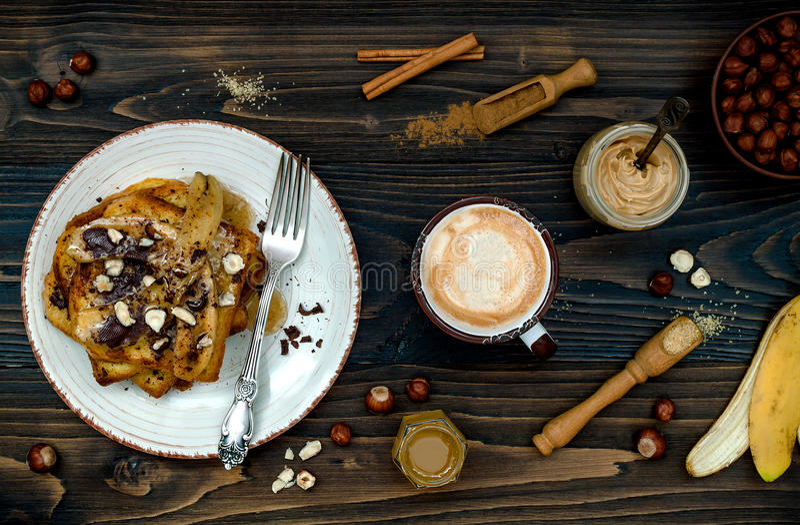 Sunt rostat bröd för vanilj för nedgång- och vinterfrukoststrikt vegetarian franskt med caramelized bananer, rå mörk choklad och  royaltyfri bild